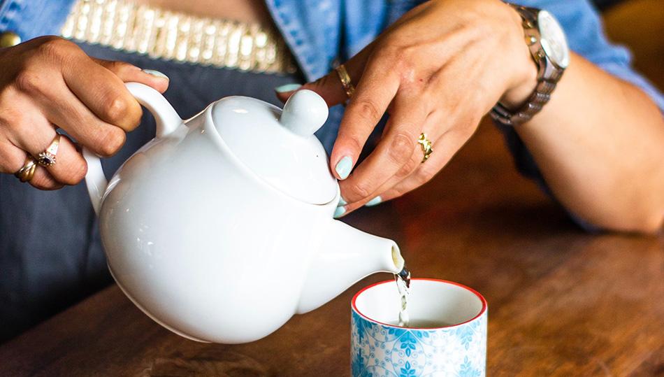 Frau mit Teetasse und Kanne - Symbolfoto
