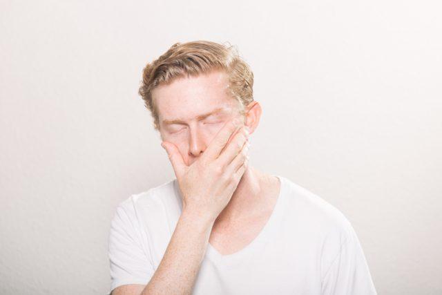 Mann mit geschlossenen Augen und Hand über Mund